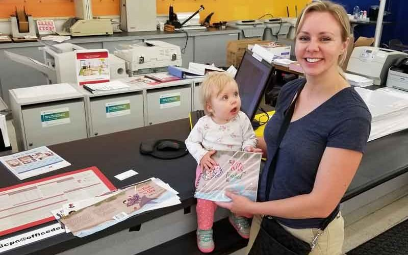 "Jenny Farmer and her daughter at the print center with a ""fresh-off-the-press"" Kumquat Kites book."